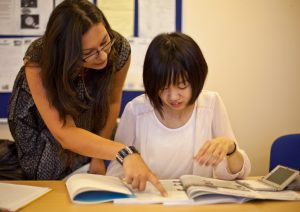 Student getting help from a General English teacher in classroom