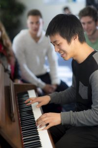 Student playing the piano in student lounge