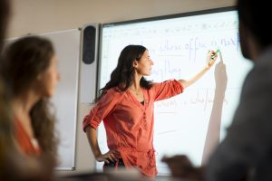 Teacher using an interactive whiteboard in a LSI Portsmouth classroom