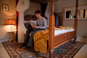 Student sitting on a bed in a LSI Portsmouth bedroom