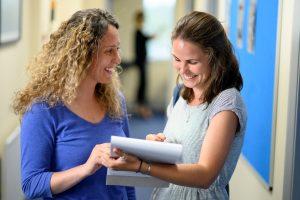 General English teacher helps student in corridor