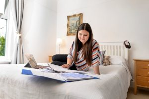A student in LSI Portsmouth accommodation on bed.