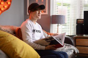Student studying LSI Portsmouth course book in living room