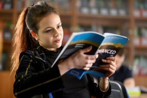 Student reading book in self-access centre