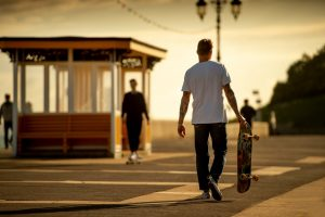 Student skateboarder walking down beach