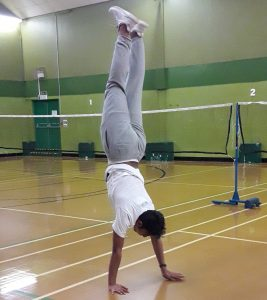 LSI Portsmouth student does a hand stand at Badminton game.