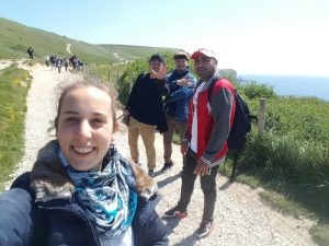 LSI Portsmouth students walk along the Jurassic coast and laugh together.