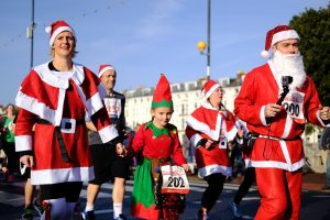 A group of Santas running down the street.